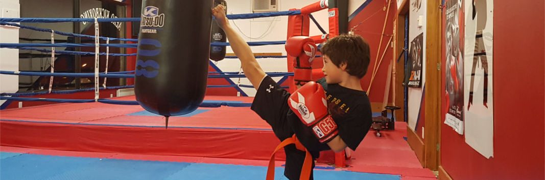 Kid practicing kickboxing, kicking punching bag.
