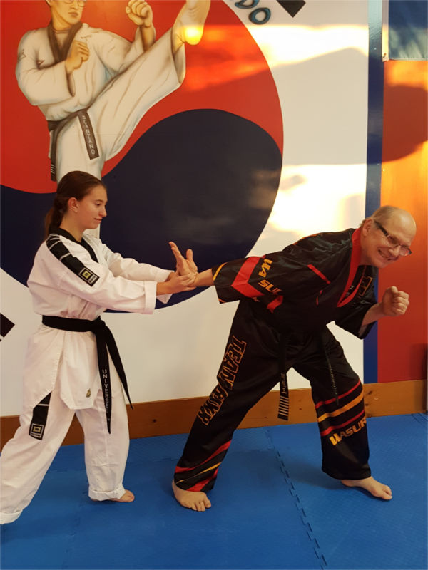 Young woman demonstrating wrist lock self-defence technique on man.